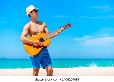 Happy traveler playing guitar on the beach in sunny day. Happy travel and vacation time concept.