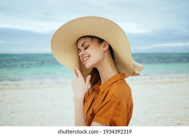 happy traveler in a sundress hat on the beach near the sea