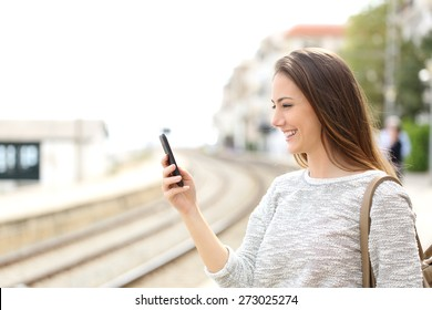 Happy traveler using a smartphone in a train station while is waiting for transport