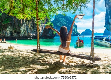 Happy traveler woman in bikini relaxing on swing and looking beautiful nature landscape Lao Lading island, Andaman sea, Krabi, Tourist sea beach Thailand, Asia, Summer holiday vacation travel trip