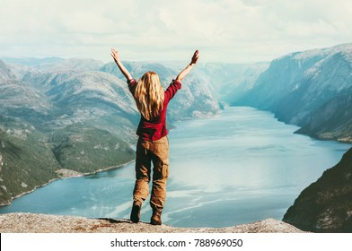 Happy traveler Woman emotional raised hands Travel adventure Lifestyle wanderlust concept vacations outdoor success walk in Norway above Lysefjord