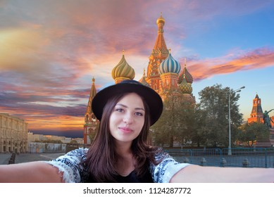 Happy traveler woman enjoying takes selfie portrait on the Red Square in Moscow