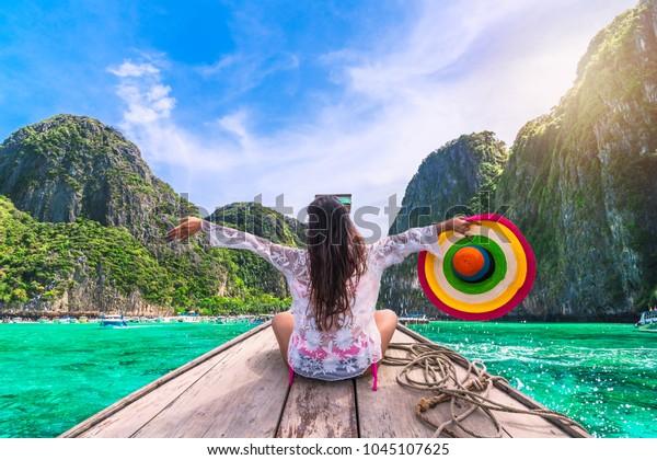 Happy traveler woman in summer dress joy fun relaxing on boat, Maya beach, Phi Phi island, Tourism Phuket, Krabi, Travel Thailand, Beautiful destination Asia, Summer holiday outdoor vacation trip