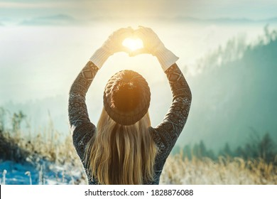 Happy traveler woman tourist stay on mountain top and making of love heart by hands in sunny frozen winter day.