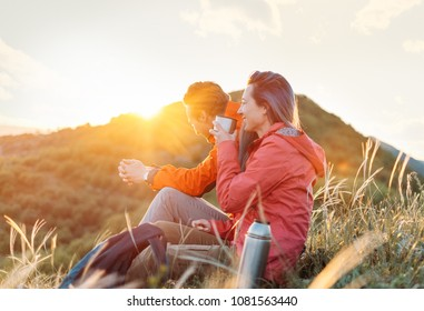 Happy traveler young couple resting in the mountains and drinking tea from thermos at sunset in spring or summer season.