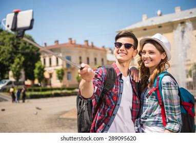Happy travelers making selfie in the street of old european city.