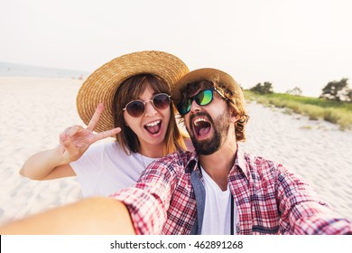 Happy  traveling  couple in love  taking a selfie on phone  at the beach on a sunny summer day.  Pretty girl and her handsome boyfriend with beard    having fun, crazy emotional faces , laughing.