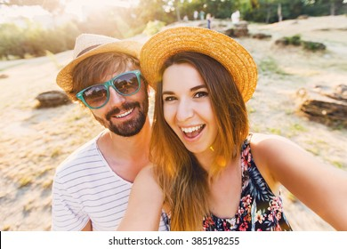 Happy traveling couple  making selfie  mountains  background , sunny summer colors, romantic mood. Stylish sunglasses, straw hat. Happy laughing  emotional faces.