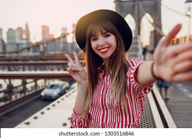 Happy traveling woman making self portrait by camera. Excited brunette female standing on Brooklyn bridge in New York. Wearing red dress and black hat.