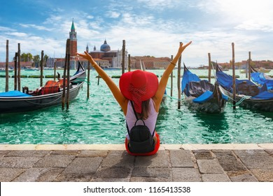 Happy traveller woman sits in front of the traditional gondolas of St. Mark's Square in Venice, Italy