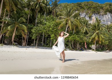 Happy traveller woman in white dress enjoys her tropical beach vacation on El Nido, Palawan, Philippines