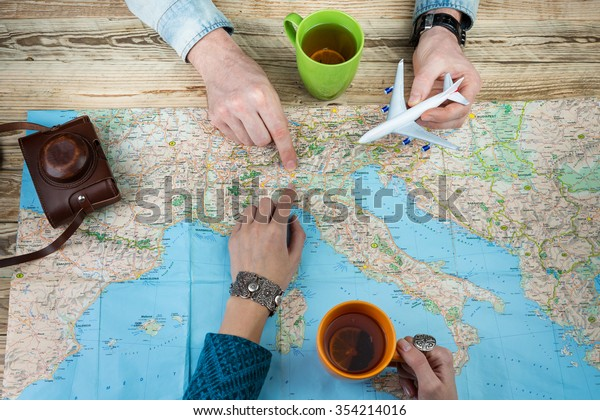 Happy travellers to Italy. Top view. Map and two people planning trip.