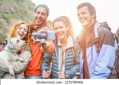 Happy trekkers people making video vlog for social network story with gimbal phone - Young hiker friends having fun on mountain excursion day - Technology trend and sport concept - Focus on right guys