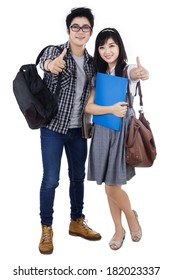 Happy trendy college students with bags and books, showing thumbs-up at camera,