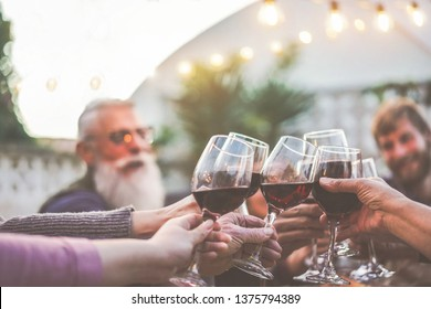 Happy trendy family cheering with red wine at barbecue dinner outdoor - Different age of people having fun at sunday meal - Food, taste and summer concept - Focus on old people hands