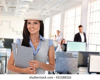 Happy trendy female office worker at busy workplace.