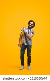 Happy trendy hipster man in skateboard skating while pointing away brightly on yellow backdrop