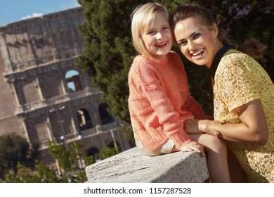 happy trendy mother and daughter travellers not far from Colosseum