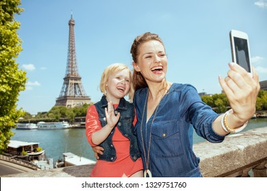 happy trendy mother and daughter travellers taking selfie with mobile phone not far from Eiffel tower in Paris, France.