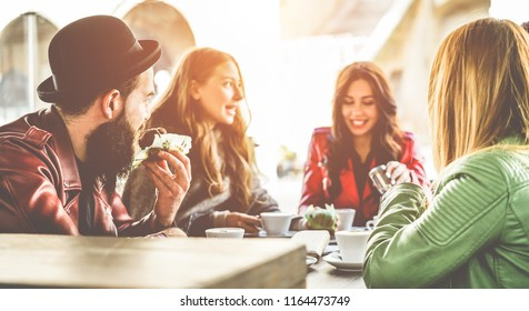 Happy trendy people having breakfast inside bar restaurant patio - Young millennials friends drinking coffees and eating muffins in morning time - Fashion and lifestyle concept - Focus on left man ear
