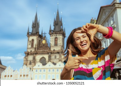 happy trendy tourist woman in colorful striped t-shirt framing with hands in Prague Czech Republic.