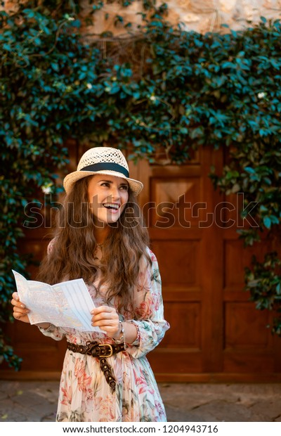 happy trendy tourist woman in long dress and straw hat with map looking into the distance in old Italian town