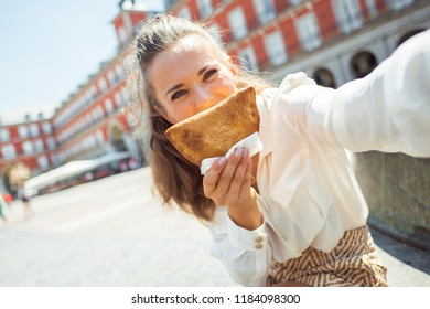 happy trendy tourist woman taking selfie while making smile with Empanada at Plaza Mayor