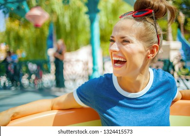 happy trendy woman in blue t-shirt in amusement park enjoying attraction.