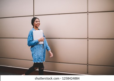 Happy trendy woman in jeans jacket holding laptop computer during walking on publicity area, young positive african hipster girl strolling near copy space area with modern technology in hands