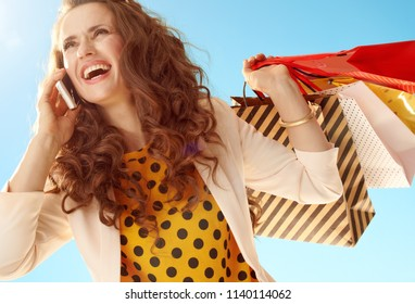 happy trendy woman in a light jacket with shopping bags talking on a mobile phone against blue sky