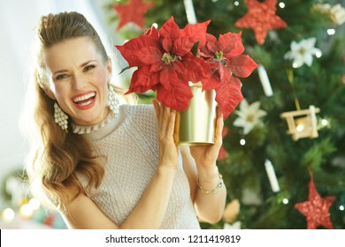 happy trendy woman near Christmas tree showing red poinsettia