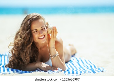 happy trendy woman in white swimsuit on the beach laying on a striped towel and listening to seashell. perfect shell - nice inexpensive souvenir. Sun protected hair. total relaxation on the best beach