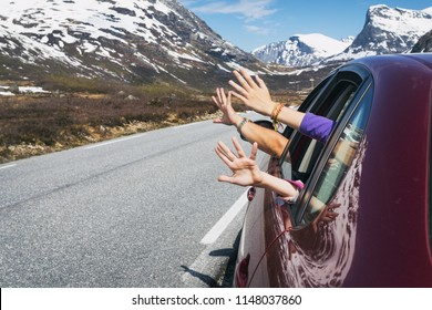 happy trip - hands of men and children peering out of the car on a background of mountains