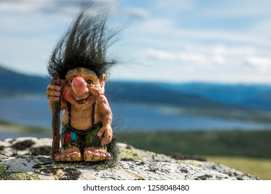 Happy troll out in the nature with his walking stick and black hair. Hair, hike, nature, wilderness, camping concept.