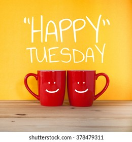 Happy Tuesday word. Two cups of coffee and stand together to be heart shape on yellow background with smile face on cup.