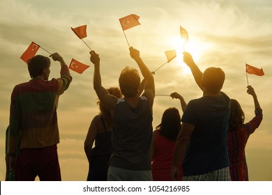 Happy turkish family with flags. Patriotic people raising flags to the evening sky, back view.