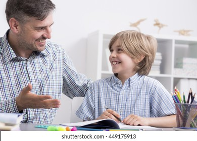 Happy tutor and small boy sitting beside desk during private lessons at home