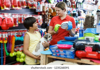 happy tweenager boy and his glad young mother looking for supplies for little dog in petshop