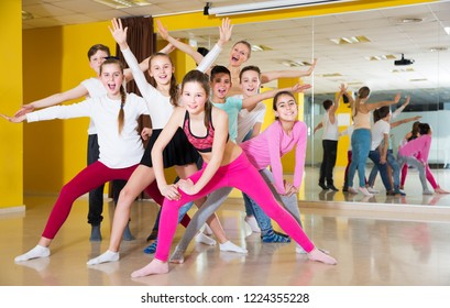 Happy tweens posing with young female trainer during dance training in modern dance school