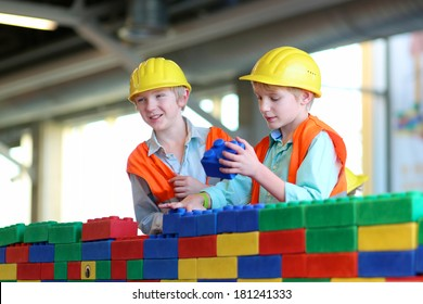 Happy twin brothers in safety helmets and high visibility jackets playing indoors building a house with big plastic construction bricks