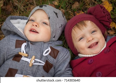 Happy twins boy and girl in autumn park