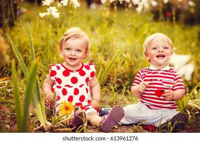 Happy twins boy and girl with flowers on summer field