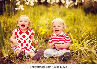 Happy twins boy and girl on summer field
