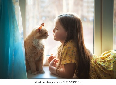 Happy twins with redhead cat at window in cozy home