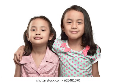 Happy two asian little girl hugging and having fun isolated over white background