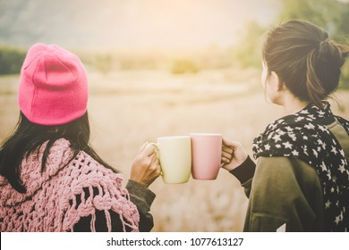 happy two Asian woman hands clink hot coffee mug outdoor  in the morning , friends enjoy drinking together cheers for two cup