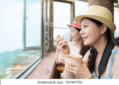 happy two Asian women tourist enjoy have famous local food taro balls in Jiufen of Taipei city, looking out great ocean view from the top of the hill.