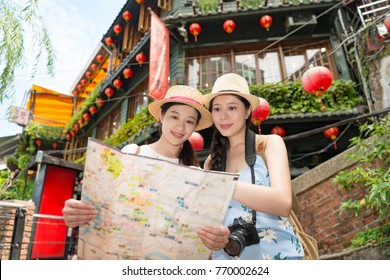happy two Asian women tourist walking around the country Jiufen of Taipei city, looking searching on the map of direction for next sightseeing landmarks.