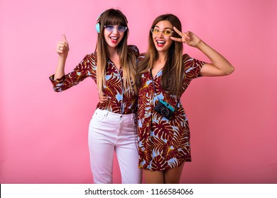 Happy two best friends sister girls having fun showing ok science, color matching tropical print clothes, colorful modern sunglasses, big headphones and vintage camera, students party.