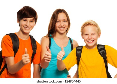 Happy two boys and a girl showing thumbs up gesture wearing school backpacks, isolated on white